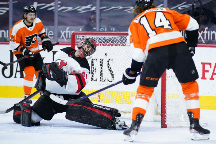 Philadelphia Flyers' Sean Couturier (14) scores a goal past New Jersey Devils' Scott Wedgewood (41) during the second period of an NHL hockey game, Monday, May 10, 2021, in Philadelphia. (AP Photo/Matt Slocum)