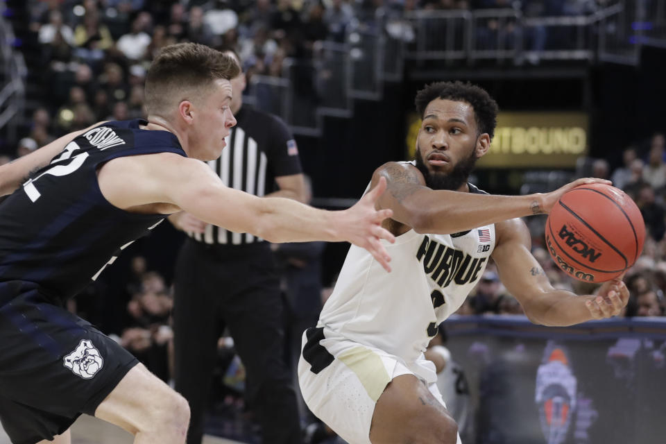 Purdue's Jahaad Proctor (3) makes a pass against Butler's Sean McDermott (22) during the first half of an NCAA college basketball game, Saturday, Dec. 21, 2019 in Indianapolis. (AP Photo/Darron Cummings)