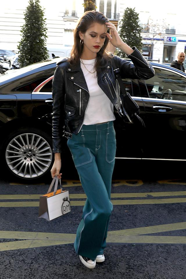 <p>In between shows, Kaia Gerber looked cool and casual in green, wide-legged jeans with a white tee and leather jacket. [Photo: Getty] </p>