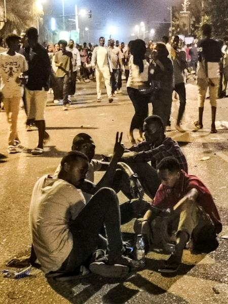 Sudanese protesters flash the victory gesture as they sit in the middle of a street in front of the military headquarters in the capital Khartoum (AFP Photo/-)