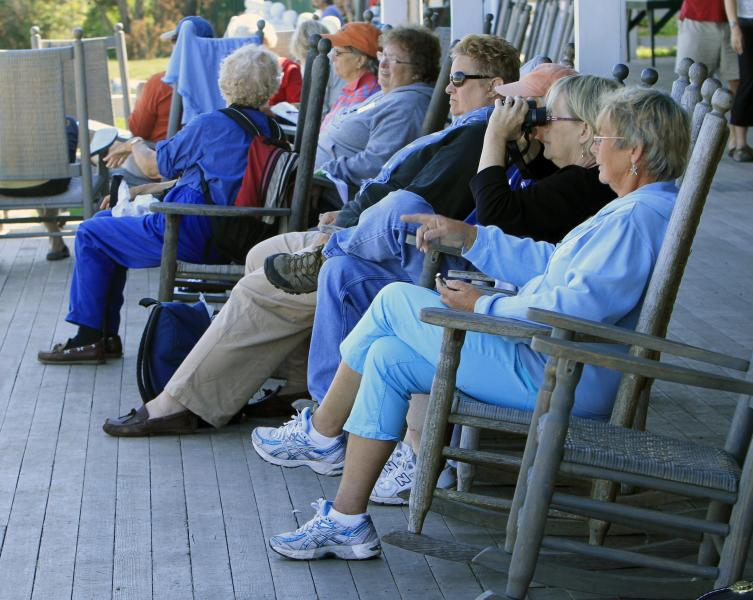 In this photo taken Friday, Sept. 14, 2012, guests sit on the veranda at the historic Star Island Family Retreat and Conference Center at the Isle of Shoals in Rye, N.H. The hotel 10 miles off the coast of New Hampshire wants to establish itself as an environmental leader. The island is essentially a self-contained system, and it is an ideal spot to showcase energy innovations and could be become a model for other communities. (AP Photo/Jim Cole)