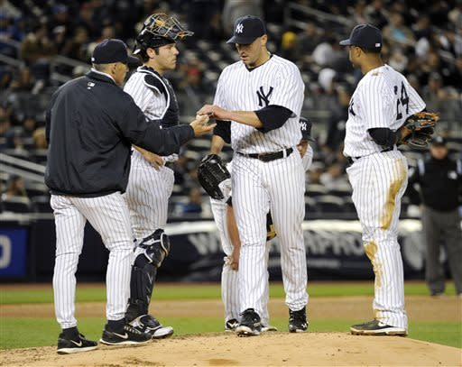 New York Yankees pitcher Andy Pettitte hands the ball to manager Joe Girardi, left, as Robinson Cano, right, and catcher Austin Romine look on during the fifth inning of a baseball game against the Houston Astros Monday, April 29, 2013, at Yankee Stadium in New York. (AP Photo/Bill Kostroun)