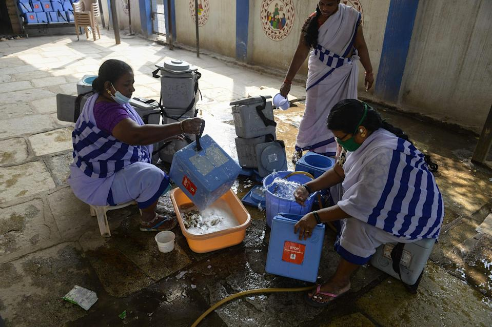 """ASHA workers clean carriers for the COVID-19 vaccine at a health center in Hyderabad on Jan. 29, 2021.<span class=""""copyright"""">Noah Seelam—AFP/Getty Images</span>"""