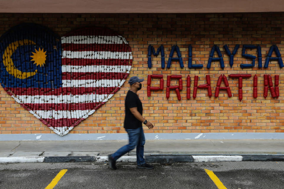 A man walks past a 'Malaysia Prihatin' wall decoration in Kuala Lumpur August 25, 2021. In giving a preview of Budget 2022's direction and approach, the ministry said it aims to ensure that those impacted by the extended movement control orders or restrictions imposed to curb Covid-19 will receive government support. — Picture by Ahmad Zamzahuri