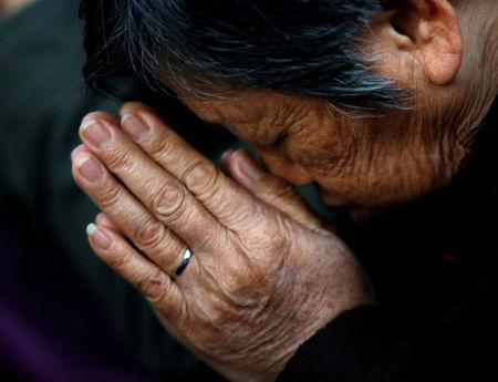 FILE PHOTO: A believer prays during a weekend mass at an underground Catholic church in Tianjin in November 10, 2013. REUTERS/Kim Kyung-Hoon File Photo