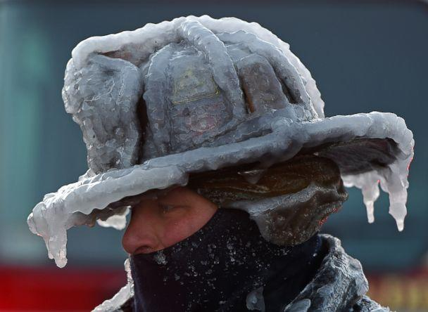 PHOTO: Firefighter Bobby Lehman, with his helmet and bunker gear caked in ice, tries to thaw out after battling a stubborn, wind-driven fire at 238 Wilson Road, Jan. 1, 2018, Nahant, Mass. (Christopher Evans/Boston Herald/Polaris)