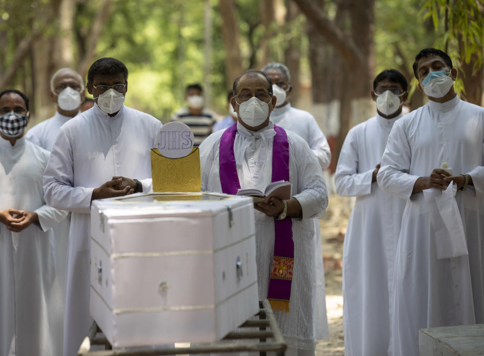 Indian Christian priests offer prayers next to the coffin of Father Rolfie D'Souza's who died of COVID-19, at a cemetery in Prayagraj, India, Saturday, May 15, 2021. India's Prime Minister Narendra Modi on Friday warned people to take extra precautions as the virus was spreading fast in rural areas. (AP Photo/Rajesh Kumar Singh)