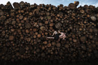 In this image released by World Press Photo, Thursday April 15, 2021, by Adam Pretty, Getty Images, titled Log Pile Bouldering, which won first prize in the Sports Singles category, shows Georg climbs a log pile while training for bouldering, in Kochel am See, Bavaria, Germany, on Sept. 15, 2020. (Adam Pretty, Getty Images, World Press Photo via AP)