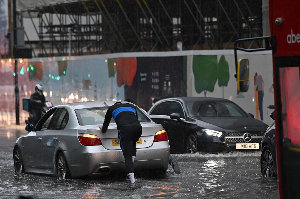 A person pushes a broken-down car through deep water on a flooded road in The Nine Elms district of London on July 25, 2021 during heavy rain. - Buses and cars were left stranded when roads across London flooded on Sunday, as repeated thunderstorms battered the British capital. (Photo by JUSTIN TALLIS / AFP) (Photo by JUSTIN TALLIS/AFP via Getty Images)