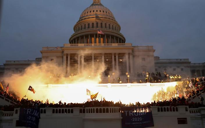 An explosion caused by a police munition is seen while supporters of U.S. President Donald Trump gather in front of the U.S. Capitol Building  - Leah Millis/Reuters