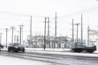 Motorist on County Road West drive past a power station Tuesday, Feb. 16, 2021, in Odessa, Texas. Many residents and businesses were left without power following a weekend of below freezing temperatures in Midland and Odessa. (Jacob Ford/Odessa American via AP)
