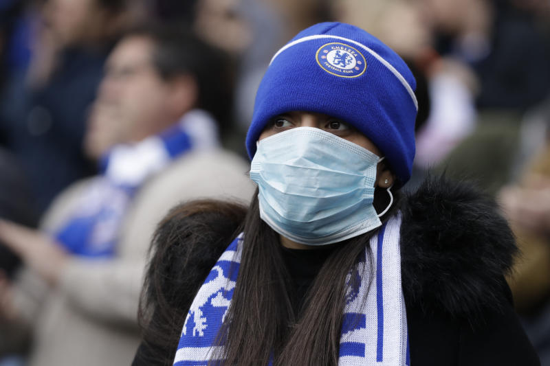 Chelsea's fan wears a sanitary mask during the English Premier League soccer match between Chelsea and Everton at Stamford Bridge stadium in London, Sunday, March 8, 2020. (AP Photo/Matt Dunham)