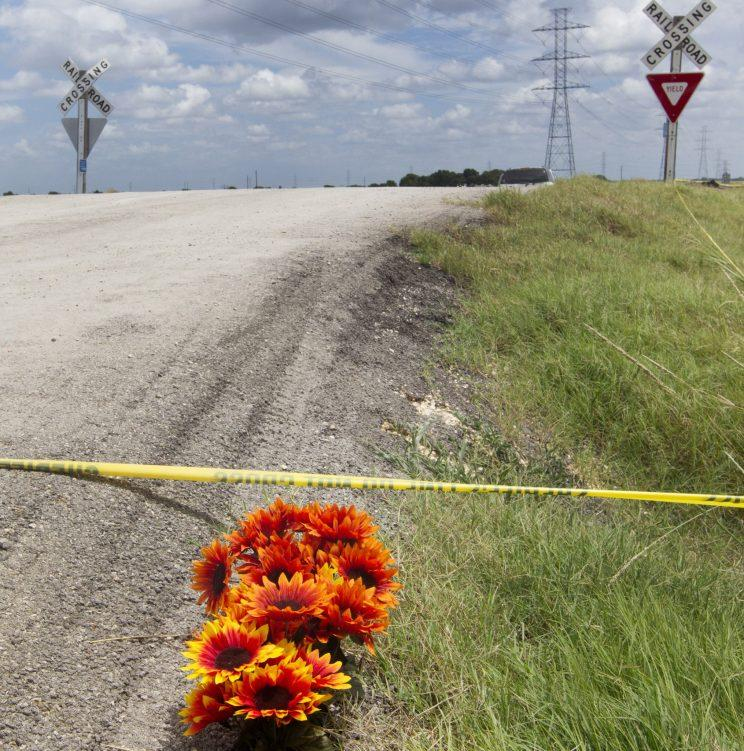Flowers sit next to police tape at the site of Saturday's hot air balloon crash near Lockhart, Texas, Sunday, July 31, 2016. (Jessalyn Tamez/Austin American-Statesman via AP)