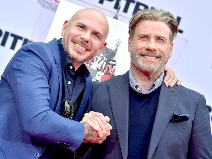 Pitbull and John Travolta at Chinese Theater footprint ceremony in December 2018 Getty Images