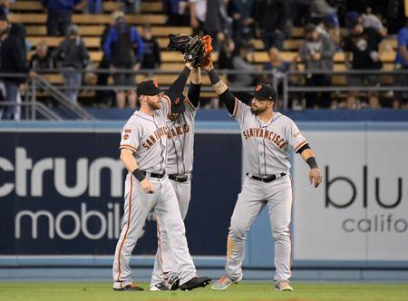 Apr 1, 2019; Los Angeles, CA, USA; San Francisco Giants outfielders Gerardo Parra (8), Steven Duggarand (6) and Michael Reed (52) celebrate after defeating the Los Angeles Dodgers at Dodger Stadium. Mandatory Credit: Kirby Lee-USA TODAY Sports