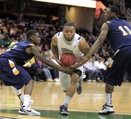 Akron's Chauncey Gilliam, center, drives between Kent State's Randal Holt, left, and Carlton Guyton, right, during the first half of an NCAA college basketball game in the semifinals of the Mid-American Conference men's tournament, Friday, March 9, 2012, in Cleveland. (AP Photo/Tony Dejak)