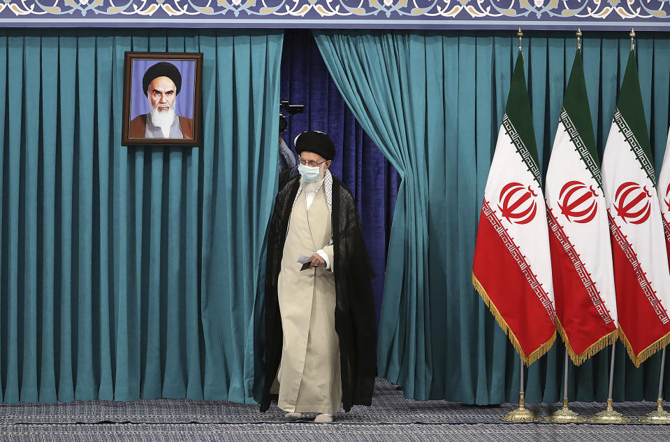 In this picture released by the official website of the office of the Iranian supreme leader, Supreme Leader Ayatollah Ali Khamenei arrives to vote at a polling station at Imam Khomeini mosque in his residence compoand, in Tehran, Iran, Friday, June 18, 2021. Iran began voting Friday in a presidential election tipped in the favor of a hard-line protege of Supreme Leader Ayatollah Ali Khamenei, fueling public apathy and sparking calls for a boycott in the Islamic Republic. A portrait of the late revolutionary founder Ayatollah Khomeini hangs at left. (Office of the Iranian Supreme Leader via AP)