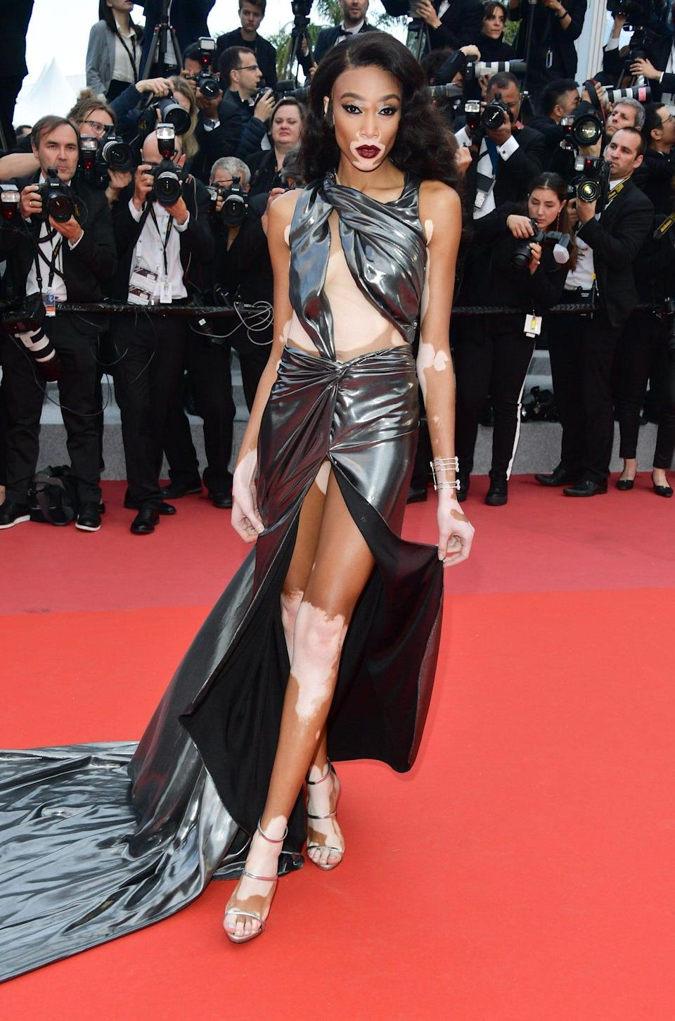Winnie Harlow wears a silver wrap dress at the 2018 Cannes Film Festival.