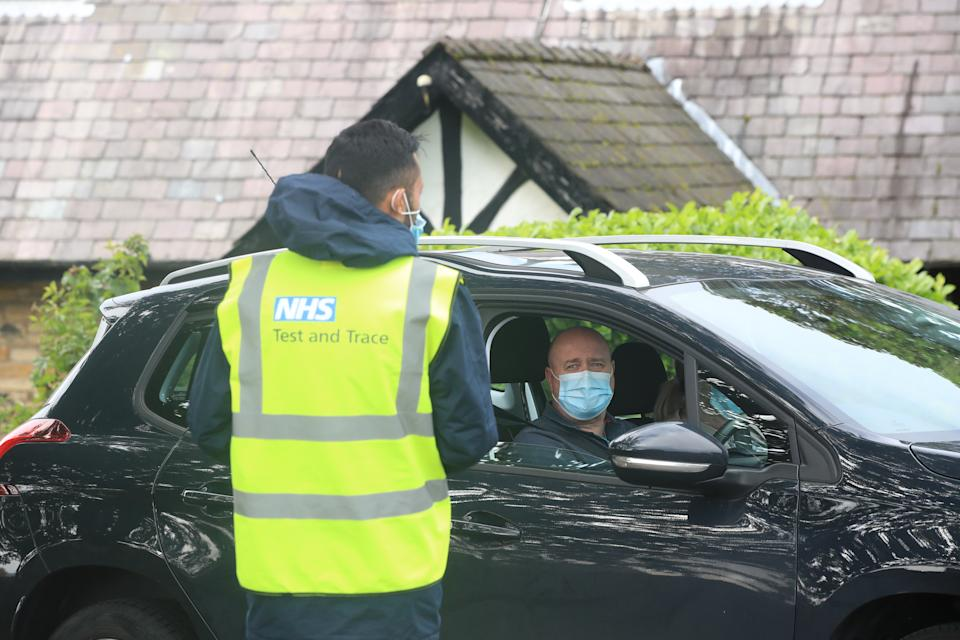 A member of staff speaking to a man (permission given) arriving at working at a Coronavirus testing centre at the Last Drop Village Hotel in Bolton.