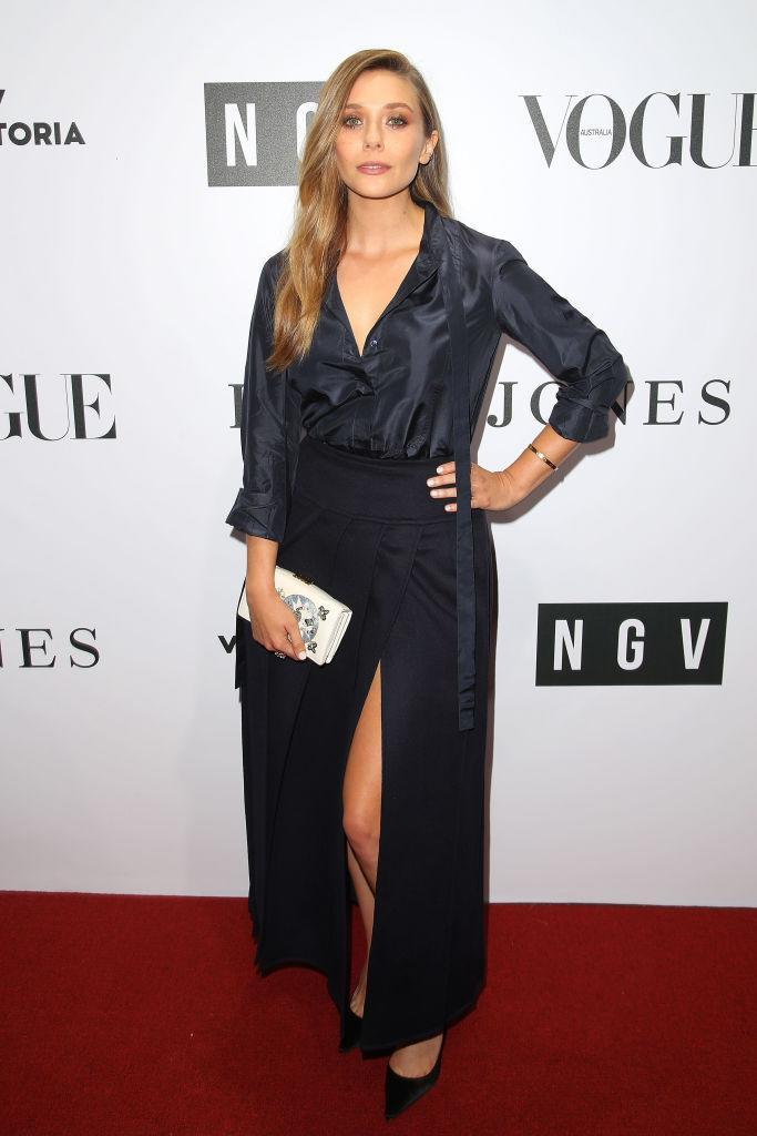 <p>Elizabeth Olsen attended the NGV Gala back in August, 2017. The actress opted for a midnight blue shirt tucked into a thigh-split skirt, both by Christian Dior. She accessorised the look with coordinating shoes by the designer and a 'La Roue de la Fortune' box clutch. <em>[Photo: Getty]</em> </p>