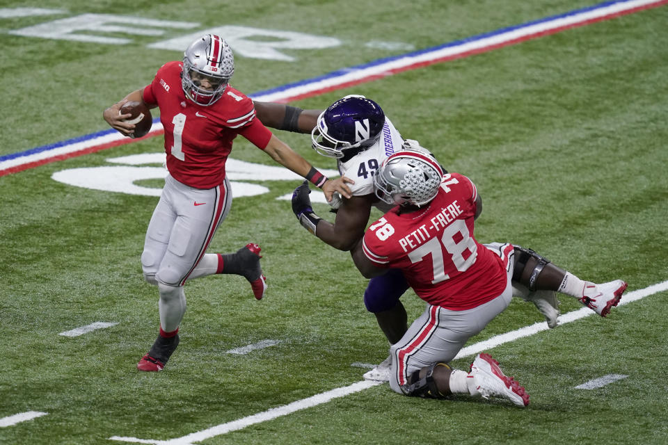 Ohio State quarterback Justin Fields (1) eludes Northwestern defensive lineman Adetomiwa Adebawore (49) as Ohio State offensive tackle Nicholas Petit-Frere (78) blocks during the second half of the Big Ten championship NCAA college football game, Saturday, Dec. 19, 2020, in Indianapolis. (AP Photo/Darron Cummings)