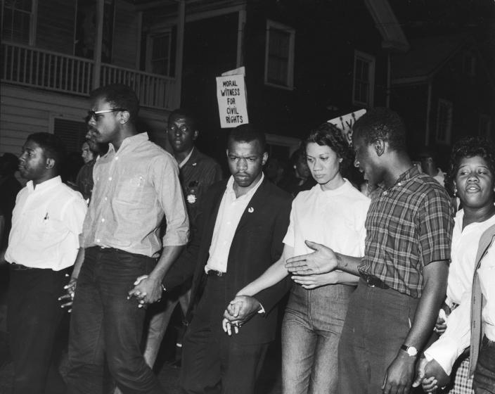 Civil Rights leaders, including future Congressman John Lewis (third left) and Gloria Richardson (third right), chair of the Cambridge Non-Violent Action Committee, links hands with others as they march in protest of a scheduled speech by pro-segregationist Alabama Gov. George Wallace in Cambridge, Md., May 1964. (Photo: Francis Miller/The LIFE Picture Collection via Getty Images)