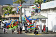 Independence supporters demonstrate with the Kanak flag outside a voting station in the Riviere Salee district of Noumea, New Caledonia, Sunday, Oct.4, 2020. Voters in New Caledonia, a French archipelago in the South Pacific, were deciding Sunday whether they want independence from France in a referendum that marks a milestone in a three-decade decolonization effort. If voters choose independence, a transition period will immediately open so that the archipelago can get ready for its future status. Otherwise, New Caledonia will remain a French territory. (AP Photo/Mathurin Derel)
