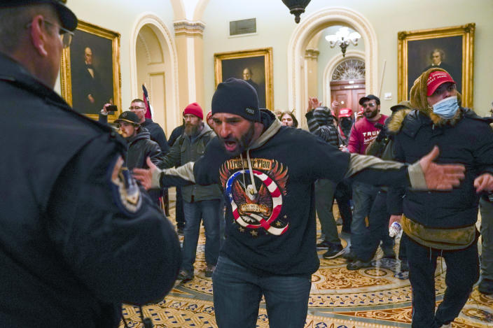FILE - In this Jan. 6, 2021, file photo, Trump supporters gesture to U.S. Capitol Police in the hallway outside of the Senate chamber at the Capitol in Washington. Doug Jensen, an Iowa man at center, was jailed early Saturday, Jan. 9, 2021 on federal charges, including trespassing and disorderly conduct counts, for his alleged role in the Capitol riot. Jensen, 41, of Des Moines, was being held without bond at the Polk County Jail and county sheriff's Sgt. Ryan Evans said he didn't know if Jensen had an attorney. (AP Photo/Manuel Balce Ceneta, File)