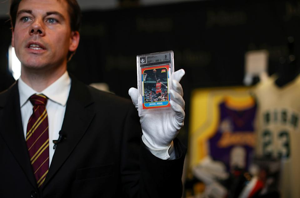 Kendall Capps, sports director at Julien's Auctions, holds a Michael Jordan Fleer card while speaking about the upcoming