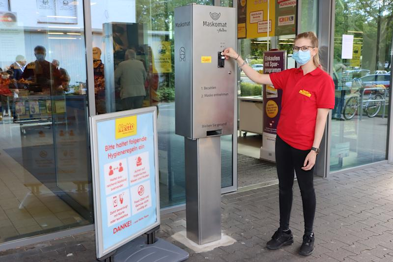 """HAMBURG, GERMANY - MAY 28: A employee of Netto market presents the first protective face mask vendor for supermarket chain Netto during the Coronavirus crisis on May 28, 2020 in Steilshoop, Hamburg, Germany. The self-service vendor called """"Maskomat"""" by Flavura is placed in front of the grocery store to provide customers with single-use protective face masks for one Euro each. (Photo by Tristar Media/Getty Images)"""