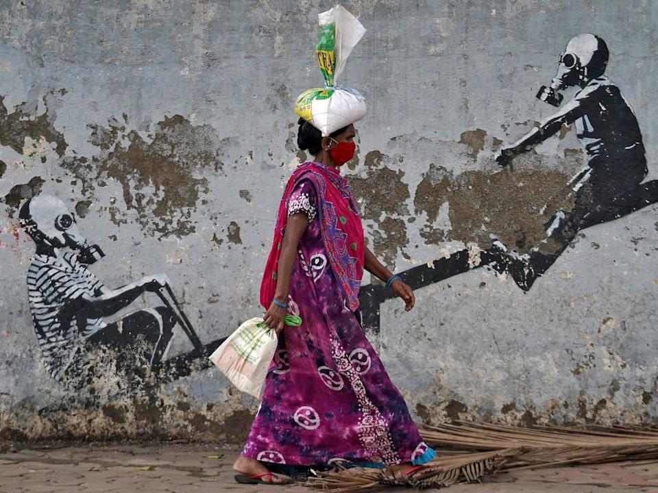 A woman wearing a protective face mask walks past a graffiti, in Mumbai, India, on June 12, 2020.