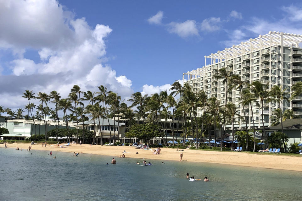 FILE - In this Sunday, Nov. 15, 2020, file photo, people are seen on the beach and in the water in front of the Kahala Hotel & Resort in Honolulu. As Hawaii struggles to control COVID-19 as the highly contagious delta variant spreads, Gov. David Ige is asking people not to visit the islands and he wants visitors and residents to limit travel to essential purposes. (AP Photo/Jennifer Sinco Kelleher, File)