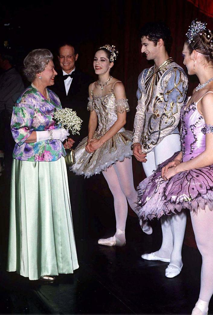 "<p>The Queen visits with dancers from ""Sleeping Beauty"" at the Royal Opera House in 1996.</p>"