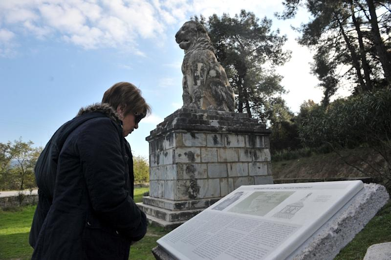 A tourist read the guide of a marble Lion statue near the site where archaeologists have unearthed a funeral mound dating from the time of Alexander the Great, in Amphipolis, northern Greece on November 22, 2014 (AFP Photo/Sakis Mitrolidis)
