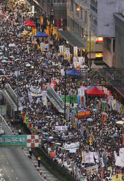 Tens of thousands of Hong Kong residents march in a downtown street during an annual pro-democracy protest in Hong Kong Monday, July 1, 2013. The protesters demanded their widely disliked Beijing-backed leader resign and pressing for promised democratic reforms so they can choose their own top representative. The march is an annual event that underscores the growing gulf between Hong Kong and the mainland 16 years after the city ceased to be a British colony and came back under Beijing's control. (AP Photo/Kin Cheung)