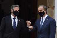 Wearing face masks bearing the G7 logo, US Secretary of State Antony Blinken, left, is greeted by Britain's Foreign Secretary Dominic Raab at the start of the G7 foreign ministers meeting in London Tuesday May 4, 2021. G7 foreign ministers meet in London Tuesday for their first face-to-face talks in more than two years. (Ben Stansall / Pool via AP)
