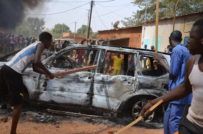 People hold wooden sticks next to damaged cars during a demonstration against French weekly Charlie Hebdo's publication of a cartoon of the Prophet Mohammed in Niamey, on January 17, 2015 (AFP Photo/Boureima Hama)