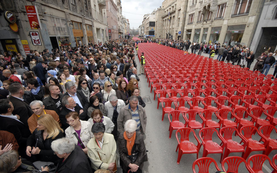 Red chairs are displayed along main street in Sarajevo to mark the 20th anniversary of the start of the Bosnian War on Friday, April 6, 2012. City officials have lined up 11,541 red chairs arranged in 825 rows along the main street that now looks like a red river. Nobody will be sitting in them since the concert being held is for 11,541 Sarajevans who were killed during the siege.(AP Photo/Sulejman Omerbasic)