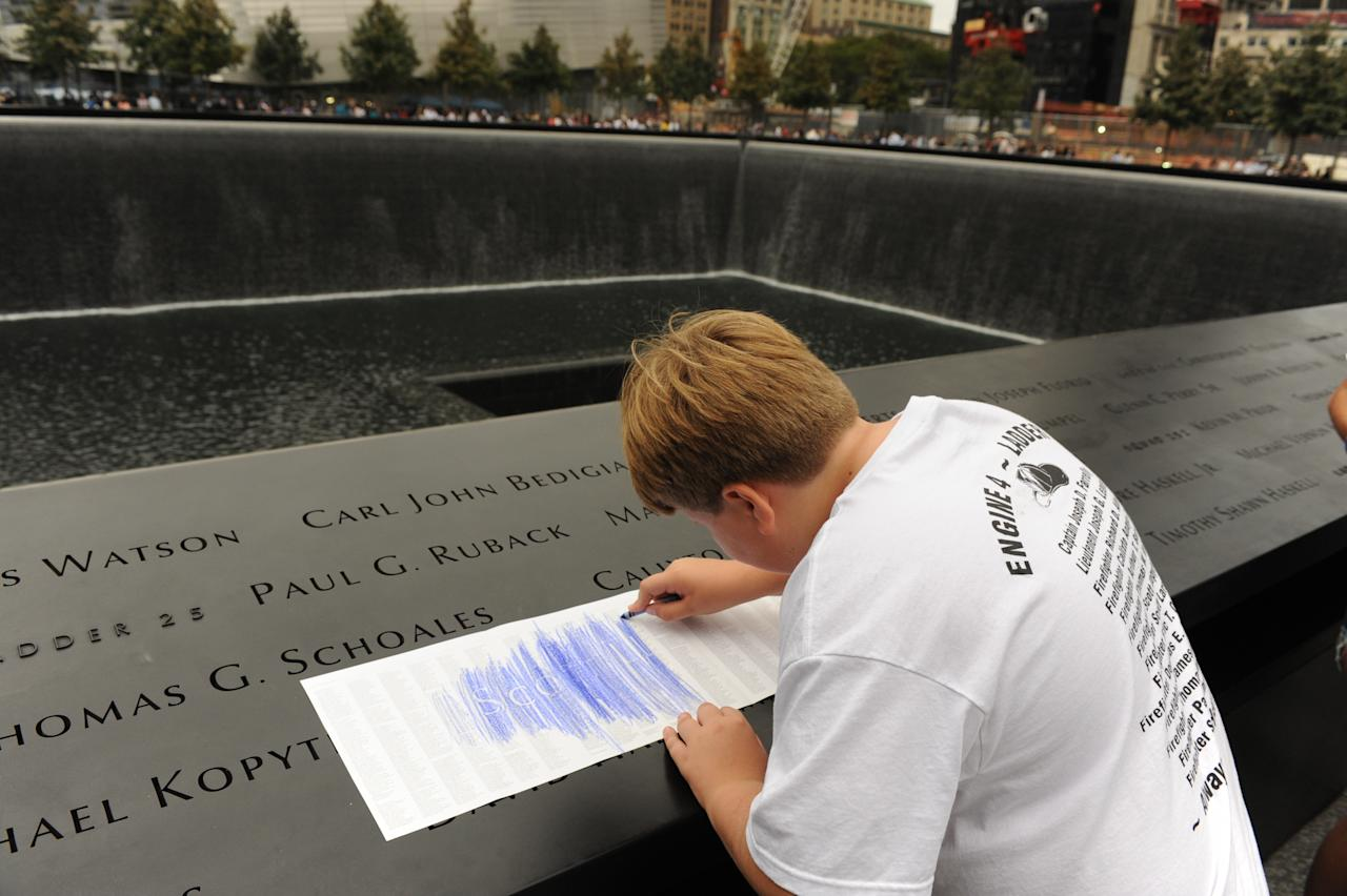 August Larsen, 9, makes an impression of his father, Scott Larsen's, name from its inscription of the wall at the Sept. 11 memorials' south pool, Sunday, Sept. 11, 2011 in New York. Sunday marked the 10th anniversary of the terrorist attacks on the World Trade Center. (AP Photo/Aaron Showalter, Pool)