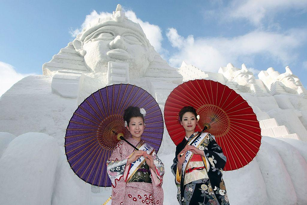 "Miss Tokamachi, Akiko Suga and Mayumi Ota pose in front of the snow sculptures ""Relics of Egypt"" prepared for Sapporo Snow Festival 2008 at Odori Park."