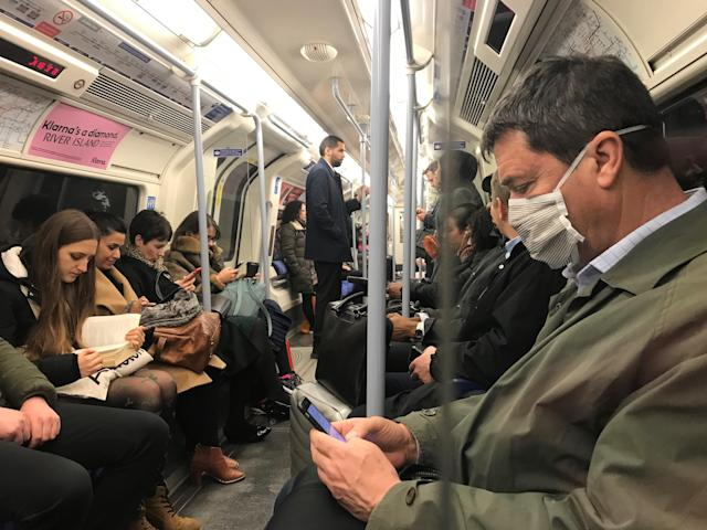 A man on the Jubilee line of the London Underground tube network wearing a protective facemask. (PA)