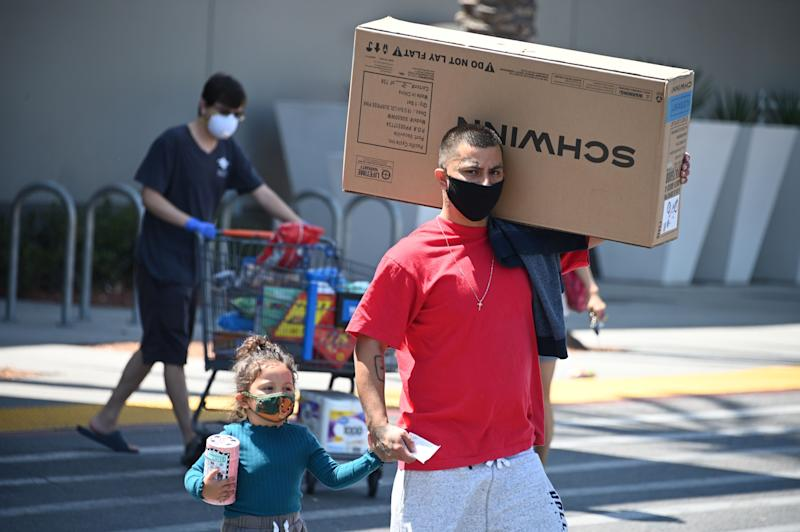 A man wearing a facemask carries a children's bicycle just purchased at Walmart as he walks back to his car, July 22, 2020 in Burbank, California. - New bicycles have been in short supply since early April when bicycle sales surged in response to the coronavirus pandemic. (Photo by Robyn Beck / AFP) (Photo by ROBYN BECK/AFP via Getty Images)