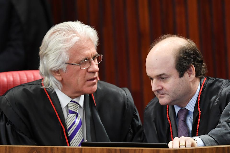 Supreme Electoral Court (TSE) Judges Napoleão Nunes Maia (L) and Tarcísio Neto talk during a session to decide whether to invalidate the 2014 presidential election because of illegal campaign funding, in Brasilia, on June 6, 2017.  At issue are allegations that when then president Dilma Rousseff ran for re-election in 2014, with Temer as vice president, their ticket was financed by undeclared funds or bribes. Both Temer and Rousseff deny any wrongdoing. / AFP PHOTO / EVARISTO SA        (Photo credit should read EVARISTO SA/AFP via Getty Images)