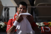 Serbia's Novak Djokovic laughs when switching ends in the second round match of the French Open tennis tournament against Lithuania's Ricardas Berankis at the Roland Garros stadium in Paris, France, Thursday, Oct. 1, 2020. (AP Photo/Alessandra Tarantino)