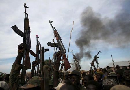 A file photo shows rebel fighters hold up their rifles as they walk in front of a bushfire in a rebel-controlled territory in Upper Nile State
