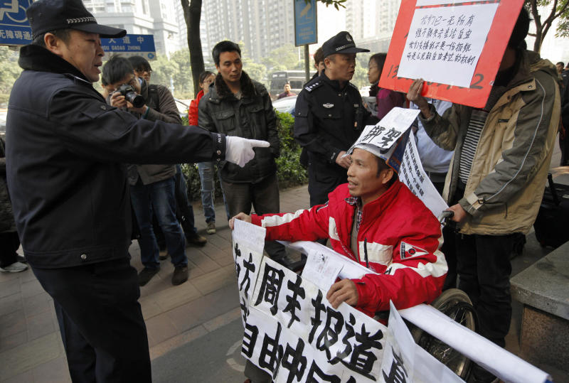 A policeman points to a supporter of Southern Weekly newspaper in a wheelchair before taken him away during a protest near the headquarters of the newspaper in Guangzhou, Guangdong province, China Thursday, Jan. 10, 2013. Police attempted Thursday to prevent more of protests outside the compound housing the Southern Weekly and its parent company, the Nanfang Media Group, in Guangzhou, a city long at the forefront of reforms. About 30 police officers guarded the area and ordered reporters and any loiterers to move away, saying there had been complaints about obstructing traffic. (AP Photo/ Vincent Yu)
