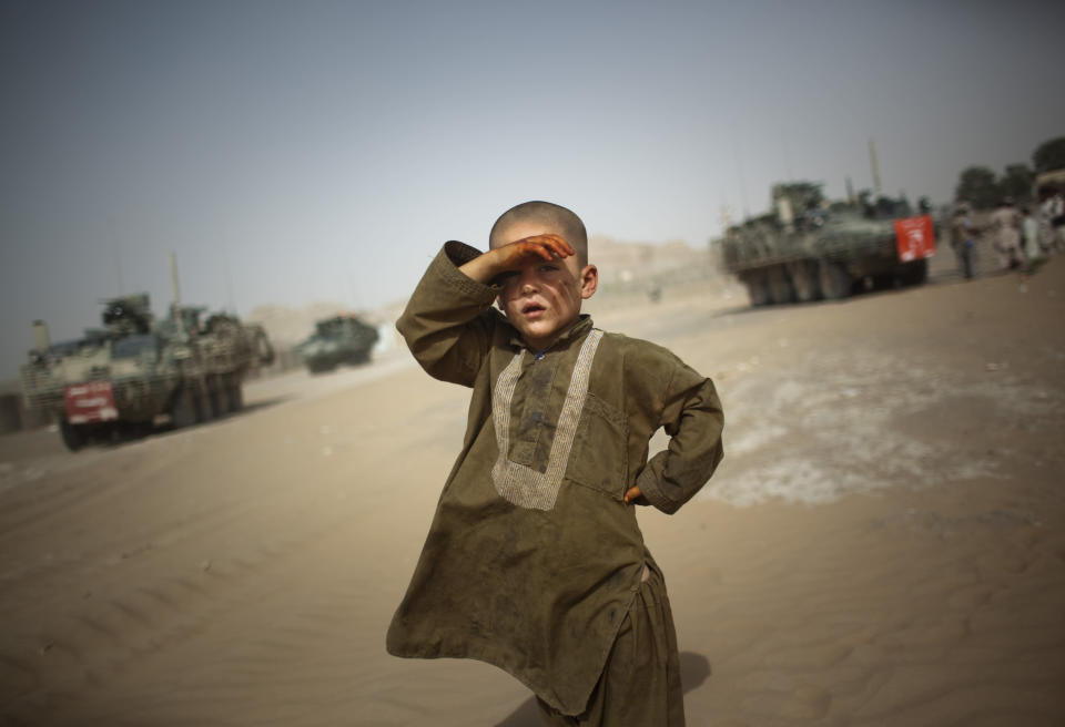 FILE - In this Aug. 6, 2009 file photo, a child watches military vehicles of 5th Striker Brigades drive past his village on the outskirts of Spin Boldak, about 100 kilometers (63 miles) southeast of Kandahar, Afghanistan. (AP Photo/Emilio Morenatti, File)