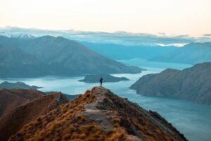 A woman looking at the beautiful landscape of the mountains and Lake Wanaka. Roys Peak Track, South Island, New Zealand. (Shutterstock)
