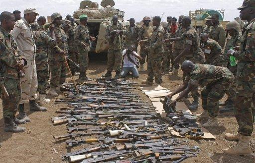 AU soldiers look at weapons recovered from members of Shebab in September