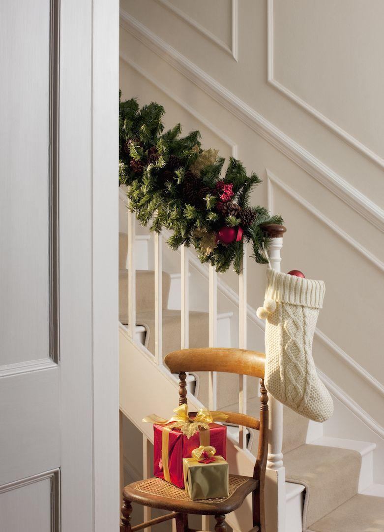 <p>Fill a simple white stocking with ornaments and hang it from the end of your banister for an easy holiday accent.</p>